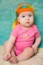 Baby girl in a pink t-shirt with scarf on a green background Royalty Free Stock Photo