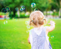 Baby girl play with soap bubbles little try to catch having fun outdoors playing games in the park happy carefree childhood Stock Image