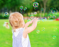 Baby girl play with soap bubbles little try to catch having fun outdoors playing games in the park happy carefree childhood Stock Photo