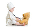 Baby girl playing doctor with teddy bear Royalty Free Stock Photo
