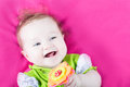 Baby girl playing with her toy flower on a pink blanket little Royalty Free Stock Image