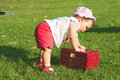 Baby girl playing with jewelry box in the garden little have got a great and beautiful gift sunny summer day green grass Royalty Free Stock Photos