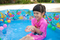Baby girl playing in kiddie pool a pink suit water and balls blue Stock Image