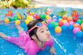 Baby girl playing in kiddie pool a pink suit water and balls blue Royalty Free Stock Photography