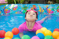 Baby girl playing in kiddie pool a pink suit water and balls blue Royalty Free Stock Images
