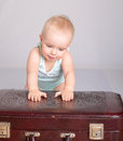 Baby girl playing with suitcase on grey background Stock Images