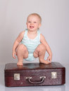 Baby girl playing with suitcase on grey background Royalty Free Stock Image