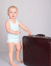 Baby girl playing with suitcase on grey background Royalty Free Stock Photos