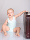 Baby girl playing with suitcase on grey background Royalty Free Stock Images