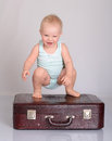 Baby girl playing with suitcase on grey background Stock Photo