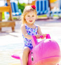 Baby girl in the pool closeup of active swimming on big pink inflatable dolphin water attractions child s camp summer holidays Royalty Free Stock Image
