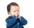 Baby girl put her finger into mouth isolated on white Royalty Free Stock Photo