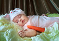 Baby girl in a rabbit hat sleeping among cabbage leaves calmly and carrot Stock Image