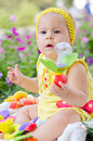 Baby girl with a rattle sitting in park in her hand Royalty Free Stock Photo