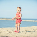 Baby girl in red dress playing on sandy beach near the sea.