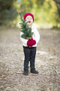 Baby Girl In Red Mittens and Cap Holding Small Christmas Tree Royalty Free Stock Photo