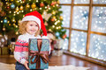 Baby girl in red santa hat holding big gift box near the Christm Royalty Free Stock Photo