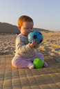 Baby girl on reed mat on beach a young sitting a the playing with a green and blue ball sun is shining the little has red Royalty Free Stock Photos