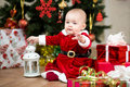 Baby girl santa claus in front of christmas tree dressed as with gifts Stock Images