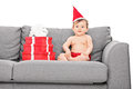 Baby girl with santa hat seated on couch little presents next to her isolated white background Royalty Free Stock Photo