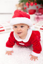 Baby girl in santa outfit crawling front of the christmas tree Royalty Free Stock Photography