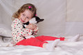 Baby girl sitting on bed and holding dog Royalty Free Stock Photo