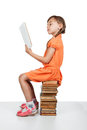 Baby girl sitting on books reading a book Royalty Free Stock Photo