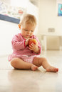 Baby Girl Sitting On Floor Looking At Apple Stock Photo