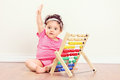 Baby girl sitting on floor and raising her hand with an abacus beside Stock Images