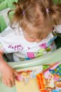 Baby girl sitting in her high chair with blonde hair tied bunches a looking at books and toys Stock Photography