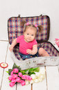 Baby girl sitting in old vintage suitcases on white flooring Stock Image
