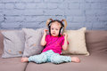 Baby girl sitting on sofa with pillows and listening to music in big headphones put on head. Royalty Free Stock Photo