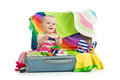 Baby girl sitting in suitcase for vacation travel with things Stock Photo