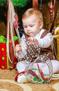 Baby girl sitting under christmas tree in room portrait Royalty Free Stock Photography