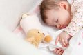 Baby girl sleeping in a cot with pacifier and toy portrait of cute stuffed Royalty Free Stock Photo