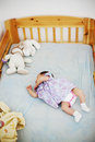Baby girl sleeping cute in her cot surrounded by some cuddly toys Royalty Free Stock Photo