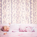 Baby girl sleeping cute tight in front of a glittering background Stock Photo