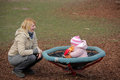 Baby girl on small carousel little cute sitting a in the park playground Royalty Free Stock Image