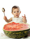 Baby girl with spoon near the large watermelon on white Royalty Free Stock Photos