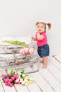 Baby girl standing near old vintage suitcases on white wooden floor in painted Stock Photography