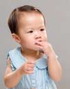 Baby girl suck finger with gray background Stock Photo