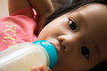 Baby girl is sucking milk from bottle before sleep. Royalty Free Stock Photo
