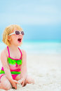 Baby girl in sunglasses sitting on beach Royalty Free Stock Photo
