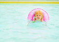 Baby girl with swim ring swimming in pool
