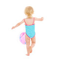 Baby girl in swimsuit playing with ball. Rear view Royalty Free Stock Photography