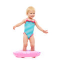 Baby girl in swimsuit standing in inflatable ring Stock Photography