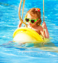Baby girl swinging on water attractions closeup portrait of cute in aquapark luxury entertainment summer resort stylish Royalty Free Stock Photos