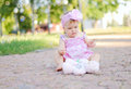 Baby girl with teddy bear in a pink dress sitting in the park Royalty Free Stock Photo