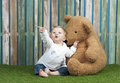 Baby girl with teddy bears seated on grass bear in font of a fence Royalty Free Stock Photos
