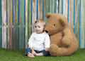 Baby girl with teddy bears seated on grass bear in font of a fence Stock Photography